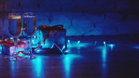 Christmas and new year gift boxes and two glasses of bubbling champagne stock footage
