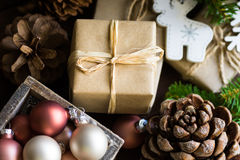 Christmas and New Year gift boxes wrapped in craft paper, twine bow, pine cones, fir tree branches, ornaments, baubles in wood box Royalty Free Stock Photos