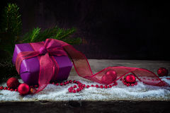 Christmas and new year gift in purple violet paper, ribbons and. Baubles on a rustic wooden board with snow, dark background with copy space Stock Photos