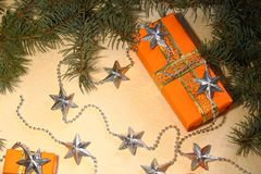 Christmas and New Year gifts in orange boxes lie under a Christmas tree next to silvery stars. Royalty Free Stock Photos