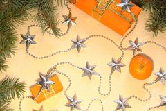 Christmas and New Year gifts in orange boxes lie under a Christmas tree next to tangerines and silvery stars. Christmas background. Boxes with gifts and Royalty Free Stock Images
