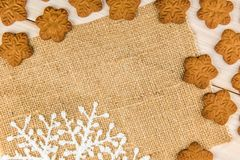 Christmas or New Year gingerbread cookies with snowflakes framed on brown sack background texture. Christmas or New Year gingerbread cookies with snowflakes stock photography