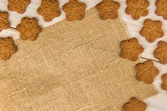 Christmas or New Year gingerbread cookies with snowflakes framed on brown sack background texture. Christmas or New Year gingerbread cookies with snowflakes stock photo