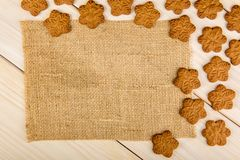 Christmas or New Year gingerbread cookies with snowflakes framed on brown sack background texture. Christmas or New Year gingerbread cookies with snowflakes royalty free stock photography