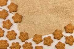 Christmas or New Year gingerbread cookies with snowflakes framed on brown sack background texture. Christmas or New Year gingerbread cookies with snowflakes stock images