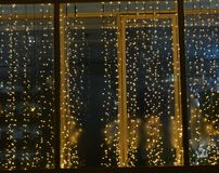 Christmas and New year golden lights on a window. Christmas and New year gold lights on a window texture background stock images