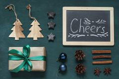 Christmas, New Year green wooden card with text Cheers. Winter holiday concept flat lay. Top view royalty free stock photography
