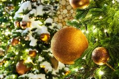 Christmas or New Year greeting card, golden christmas decorations glass balls on green pine branches, white snow and shiny lights royalty free stock photo