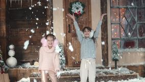 Christmas or New Year. happy children throw up snow. two little girls in fur headphones. Two little girls on the porch. Christmas or New Year. Children in light stock video footage