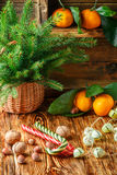 Christmas. New year. Holiday card - basket, fir branches, tangerines, hazelnuts, walnuts, candy canes and garland Stock Photography