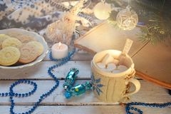 Christmas and new year holiday celebration concept background. Cup of cocoa with marshmallow, homemade chocolate cookie and peanut. Biscuit, lighted candles Royalty Free Stock Photo