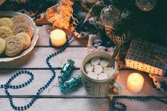Christmas and new year holiday celebration concept background. Cup of cocoa with marshmallow, homemade chocolate cookie and peanut. Biscuit, lighted candles stock images