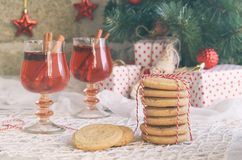 Christmas and new year holiday celebration concept background. Glass of mulled wine with spices, homemade cookie, xmas tree decora. Tion on wooden table royalty free stock photos