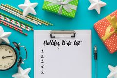 Christmas and New Year holiday to do list with notepad, pen, gift boxes, clock, cocktail tubes, stars on the blue Royalty Free Stock Image