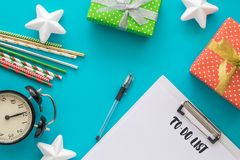 Christmas and New Year holiday to do list with notepad, pen, gift boxes, clock, cocktail tubes, stars on the blue royalty free stock photography