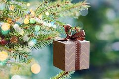 Christmas and New Year holidays card. Gift box hanging on Christmas tree branch on blue green background royalty free stock photos