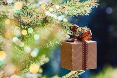 Christmas and New Year holidays card. Gift box hanging on Christmas tree branch on blue green background stock images