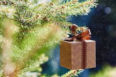 Christmas and New Year holidays card. Gift box hanging on fir branch on blue green background royalty free stock photos