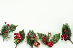 Christmas New Year holidays composition: 5 green branches, red berries and gift. On white background with copy space for your text. Merry Christmas royalty free stock photography