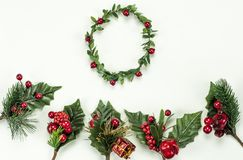 Christmas New Year holidays composition: green holiday wreath, five green branches, red berries and gift. On white background with copy space for your text. Red royalty free stock images