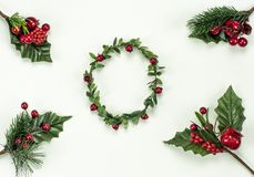 Christmas New Year holidays composition: green holiday wreath, 4 green branches, red berries and gift. On white background with copy space for your text. Merry stock image