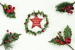 Christmas New Year holidays composition: green holiday wreath with red star, 4 green branches, red berries and gift. Christmas New Year holidays composition royalty free stock photos