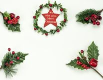 Christmas New Year holidays composition: green holiday wreath with red star, 4 green branches, red berries. On white background with copy space for your text royalty free stock image