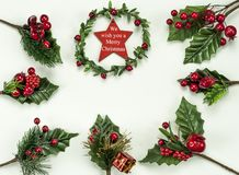 Christmas New Year holidays composition: green holiday wreath with red star, 7 green branches, red berries and gift. On white background with copy space for royalty free stock photos