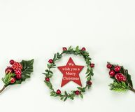 Christmas New Year holidays composition: green holiday wreath with red star, 2 green branches, red berries and gift. On white background with copy space for stock image