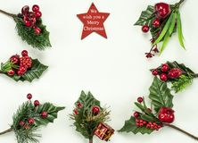 Christmas New Year holidays composition: red star, 7 green branches, red berries and gift. On white background with copy space for your text. We wish you a royalty free stock photography