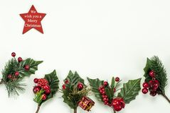 Christmas New Year holidays composition: red star, five green branches, red berries and gift royalty free stock images