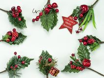 Christmas New Year holidays composition: red star, 8 green holiday branches, red berries and gift. On white background with copy space for your text. Red star royalty free stock images