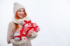 Christmas and New Year holidays. Happy woman holding gift boxes on white background in black friday. Copy space. Stock Photos
