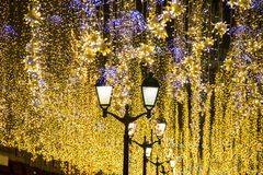 Christmas and New Year holidays illumination outdoor in city street at night. Golden shimmering. And waving garlands with classical street lights stock image