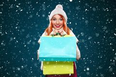 Christmas and New Year holidays.. Shopping woman holding color bags and on winter background with snow in black friday Stock Photos