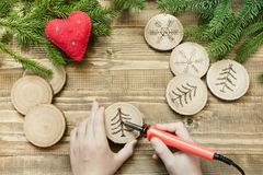 Christmas or New Year homemade pyrography toys. Wooden slice. Alternative decor. Xmas decorations. Child makes gifts for relatives Royalty Free Stock Images