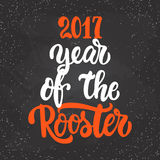 Christmas and New Year lettering calligraphy greeting card with 2017 year of the red fire rooster on the black. Christmas and New Year lettering calligraphy Royalty Free Stock Photos