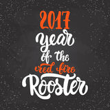 Christmas and New Year lettering calligraphy greeting card with 2017 year of the red fire rooster on the black Stock Images