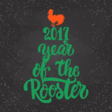 Christmas and New Year lettering calligraphy greeting card with 2017 year of the red fire rooster on the black Royalty Free Stock Photos