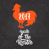 Christmas and New Year lettering calligraphy greeting card with 2017 year of the red fire rooster on the black. Christmas and New Year lettering calligraphy Stock Photo