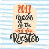Christmas and New Year lettering calligraphy greeting card with 2017 year of the red fire rooster on the blue striped. Christmas and New Year lettering vector illustration