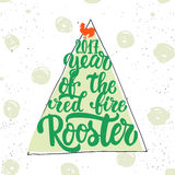 Christmas and New Year lettering calligraphy greeting card with 2017 year of the red fire rooster. Cock silhouette on. The top of illustration. Symbol of Stock Photos