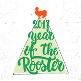 Christmas and New Year lettering calligraphy greeting card with 2017 year of the red fire rooster. Cock silhouette on. The top of illustration. Symbol of Royalty Free Stock Photography