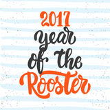 Christmas and New Year lettering calligraphy greeting card with 2017 year of the red fire rooster on the striped. Christmas and New Year lettering calligraphy Royalty Free Stock Image