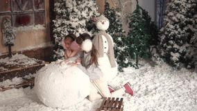 Christmas or new year. children make a snowman. two little girls make a ball of snow. Christmas or New Year. a little girl hanging decorations on a Christmas stock video footage