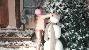 Christmas or new year. the child adjusts his hat and scarf on the snowman stock video footage