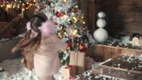 Christmas or new year. portrait of a little girl in Christmas decorations. a child throws snow up and smiling stock footage