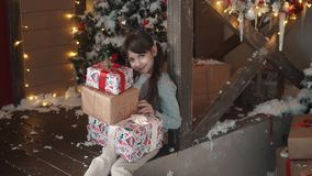 Christmas or new year. little girl holding in hands a box with gifts and smiles slyly. the child received many presents stock video
