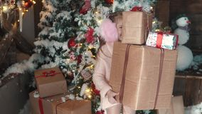 Christmas or new year. little girl holding in hands a box with gifts and smiles slyly. the child received many presents stock footage