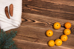 Christmas and New Year Mandarins in the form of a smile, next to the Christmas tree branches with cones on a wooden background. A Christmas and New Year Royalty Free Stock Image